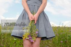 Young woman on wildflower meadow holding flowers Stock Photo - Premium Royalty-Free, Image code: 641-07766028