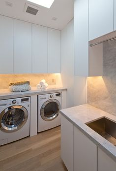This laundry room is full of cabinets and has a skylight for adding natural light to the room.
