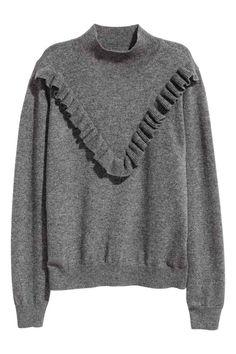 Fijngebreide kasjmier trui: PREMIUM QUALITY. Een fijngebreide trui van kasjmier met een gebreide volant bovenaan. De trui heeft een turtleneck en een ribgebreide boord aan de onderkant en onder aan de mouwen.