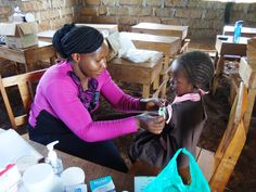 Community Health Nurse Winjoy attends to a young student. #publichealth #Kenya