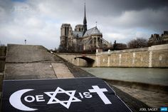 """FRANCE, Paris: A poster by French street artist Combo is pictured after being stuck on the Quai de la Tournelle, near the Arab World Institute (IMA) on February 8, 2015 in Paris, displaying Combo's message on the  coexistence of religions, using intertwined symbols of the Muslim,  Jewish and Catholic religions to write the word """"Coexist"""". Combo stuck  and distributed posters in front of the Arab World Institute (IMA) in  Paris on February 8, supported by the ..."""