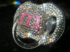 Pretty, but be careful with this one.  Maybe it's just a keepsake... BLINKY'S inital rhinestone pacifier with crystal bling. $35.00