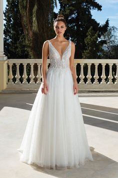 Romantic and elegant. This ball gown features a plunge illusion bodice adorned with floral patterned beading and pearls. The illusion side cutouts with pearls make the look more modern. For a more classic style, a plain tulle skirt is also available. For a more classic style, a plain tulle skirt without the pearls is available. This style can also come with a raised neckline option or with the front bodice lined to the side illusion inserts.