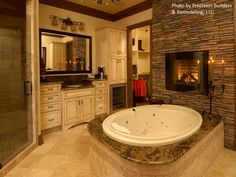 A traditional tuscan style master bathroom with a jacuzzi tub and fireplace, dark crown molding, beige tile flooring and off white glazed raised panel cabinetry.