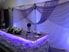 Lilac & white backdrop with uplighting and head table display with rope lighting for an added touch.