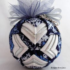 A brother to last season's Ember, Emerson has hit the scene and is positively striking with his rich, royal colors of blue, white, and silver. He is a real eye catcher and promises to look exquisite on any tree! Each ornament is three inches in diameter and is crafted using a combination of fabrics, ribbons, and over 200 straight pins. For this reason, care should be taken to keep these ornaments out of the reach of children and animals.