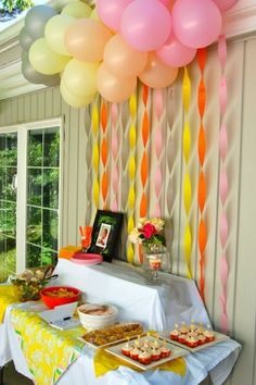 red blue and green balloons and streamers behind the food table?