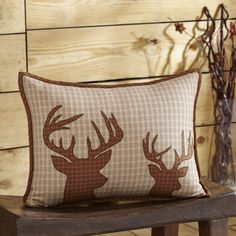 """The Tallmadge Deer Pillow features two antlered bucks in deep brown, appliqued on natural, brown and red plaid fabric. This pillow brings a bit of the great outdoor wildlife into your cabin in neutral tones to compliment a lodge theme. Straight edge with .5"""" bias cut deep brown check. Reverses to same natural, brown and red plaid as front with 2-tie closures. 3"""" overlap to conceal pillow insert (fill pillow insert is included).  Measures 14"""" x 18""""."""