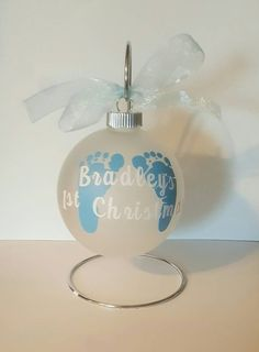 Commemorate your childs first christmas with this adorable personalized ornament. Featuring baby feet with childs first name. Year is placed on the back of the bulb. Ribbon bow is applied and can be used for hanging. Bulb is 3.25 inches and frosted glass. Vinyl decal is designed and cut with my machine using high quality indoor vinyl. Be sure when checking out to include the name of the baby and the year in the notes to seller section.