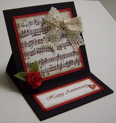 """STAMPS: Musical Notes Wheel. PAPER: Basic Black, Whisper, Real Red. INK: Chocolate Chip, Soft Suede. OTHER: Wheel Guide, 5/8"""" Real Red Satin Ribbon (approx. 10""""), 5/8"""" Old Olive Satin Ribbon (approx.4""""), Crocheted Lace (approx. 12""""), Kaiser Pearl Brad, Flourish Embossing Plate, Eight Small Red Half-Pearls, Heart Punch, Stickles, Small Hole Punch, Sticky Strips, Dimensionals."""