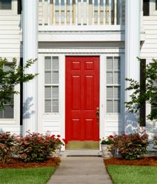 The entry, a six-paneled door, is red and has a bronze kick-plate. On both sides… Front Door Paint Colors, Painted Front Doors, Front Door Design, Glass Front Door, Christmas Classroom Door, Black Front Doors, Colonial Style Homes, Favorite Paint Colors, Exterior Paint