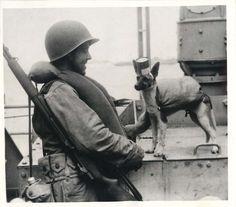 """1943- U.S. soldier with Army mascot dog """"Freddie"""" who is wearing helmet made from an empty food can and a makeshift lifebelt aboard a transport enroute to war zone."""