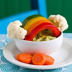~Over the Veggie Rainbow~ This Saint Patrick's Day snack provides a golden opportunity to entice your kids to eat fresh vegetables. ~To make: *Fill small bowl w/dip (we used guacamole, or use Ranch). *Slice 4 long strips of bell peppers in various colors, arrange as shown. *Cut 2 small cauliflower clouds, skewer each w/toothpick, position one on each side of peppers. *Place sliced carrot coins beside the bowl for the leprechaun's pot of gold.
