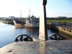 STRANGE ABANDONED RUSSIAN SUBMARINE - STORED AMONG OTHER JUNKED VESSELS (Looks like a Typhoon given the scale and twin ducted screws)