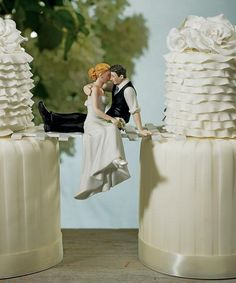 """""""The Look of Love"""" Wedding Cake Topper made of hand painted porcelain.  The bride is wearing an elegant white dress while the groom is wearing a black suit without a jacket with rolled up sleeves.  They are posed sitting, while the groom holds his bride in his arms, stealing a kiss."""