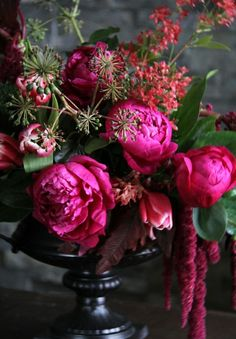 Peonies in a dark wood urn....