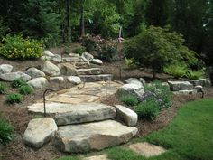 A boulder wall, landscape steps, stone edging on a short landing of flagstone walkway, trees, shrubs, and a large block retaining wall. Landscaping lighting also lines the walkway.  Picture compliments of www.nichegardenslandscaping.com