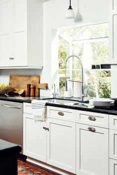 Kitchen with large glass window, white walls, white cabinets, black countertops, and red patterned rug