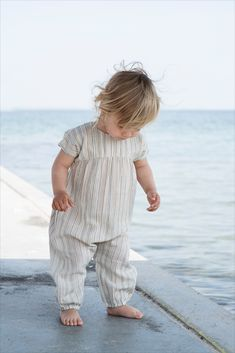 Serendipity Organics Baby Puff Suit.  Multi stripe baby suit in organic woven cotton. The suit has a loose fit at practical pushbuttons at the neck and between the legs for diaper change. So cute for warm summer days with the matching hat.  Organic and GOTS certified
