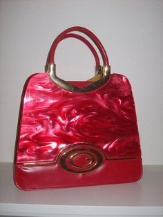 This fantastic red vintage handbag wont last long! Beautigul brass accents with gold G logo on the front. Shiny red swirled celluloid front. Two large inner compartments. Lots of zippered pockets. No tags or identification. A very unique and wonderful purse to add to your collection. Get looks and compliments every day! Only from Retro Realm