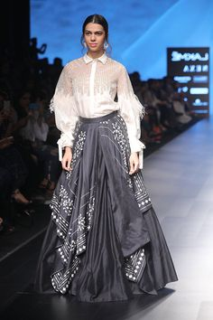Black draped skirt with shirt Featuring a black draped skirt tailored in silk with contrast detailing on it paired with an ivory flared sleeve shirt in silk and hand made mesh accented with geometric pattern and fringes. Engagement Dress For Female, Indian Engagement Dress, Engagement Dresses, Designer Wear, Designer Dresses, Draped Skirt, Bridal Lehenga, Dress Patterns, Dresses Online
