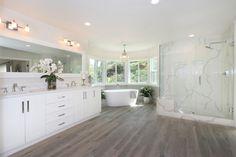 Master bath with Calcutta Quartz Classique slab shower, custom vanity, wood grain tile floors and standalone tub. Wood Grain Tile, Stand Alone Tub, Custom Vanity, Real Estate Information, Local Real Estate, Double Vanity, Master Bath, Floors, Tile Floor