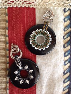 Two embellished black onyx donuts using various sizes of metal and glass seed beads.