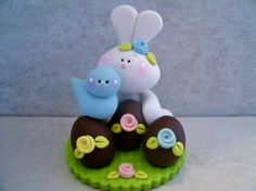 A white bunny has a trio of chocolate Easter eggs...he is a accompanied by a little blue bird!  This is an original design that was handcrafted from polymer clay. The piece stands approximately 2 1/2 tall and all parts have been secured with liquid polymer for increased strength.    Not a toy...not suitable for young children.