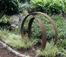 Old rusty farm parts as garden sculptures