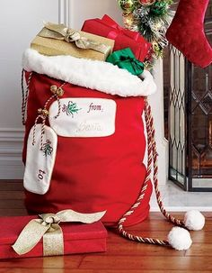 Imagine the delight of finding one of our Personalized Santa Bags with your name on it under the tree. This generously sized bag is made of plush, heavy felt with faux fir trim, embellished with sparkling twisted rope cording. Brass plated jingle bells and tassels add the finishing touches.