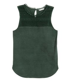 Sleeveless top in soft jersey with lace at front, opening at back of neck with a button, and a rounded hem.