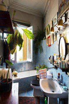 Crazy, kooky little bath; I love it. That blue tile, all the artwork, the odd triangular shape of the room...