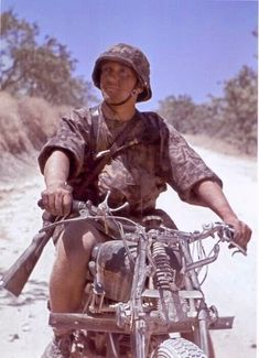A Grenadier from Hermann Göring Division in Tunisia, 1943. He ride an Italian Bianchi motorcycle (produced in 1936-1940 period). Not enough of the bike is shown to identify the model, but possibly a 500cc model. He also wears SS-Palmenmuster camo uniform