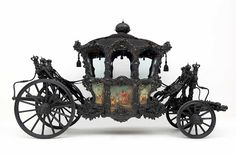 "State Coach, so-called ""Mourning-Homage-Carriage""1720 - 1780. The originally gold-plated, high-ranking state coach was adapted to a mourning carriage in the early 19th century and was painted and fitted out in black. The allegorical paintings on the coach panels by Michelangelo Unterberger were only rediscovered under the black paint in 1930. This carriage was also drawn by six or eight white horses from the Kladrub imperial stud farm."
