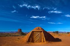 Hogan, the traditional Navajo red clay earth house, with backdrop of famous table mountains of the Navajo National monument on the background  ~ George Burba see inside @ http://tinyhousetalk.com/navajo-hogan-dwellings/
