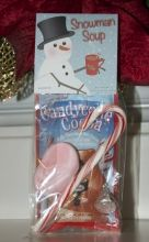 Take a single-serving package of hot chocolate mix, chocolate candy kiss, marshmallows and candy cane, package in a mug or holiday-themed goody bag, then add a free printable gift tag or bag topper for a cheery winter gift.