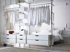chambre blanche avec penderie équipée d'armoires à tiroirs blanches et étagères verticales