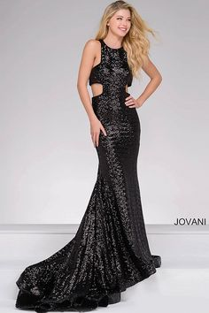 Long black all-over sequined gown features a high neckline, side cutouts, a zipper in the back and a long elegant train in the back.