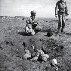 March 16, 1945: Fighting on Iwo Jima ends.    Pictured: American troops chat near a dead Japanese soldier on Iwo Jima. The degree to which the Japanese were willing to fight to the death, rather than surrender, is summed up in one remarkable statistic: Close to 20,000 Japanese soldiers were killed during the battle; only around 200 were captured.