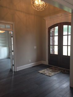 "The Entry  7"" engineered oak hardwood plank flooring in a Lone Star Gray satin finish 8' Mahogany Entry Doors stained in Dark Walnut"
