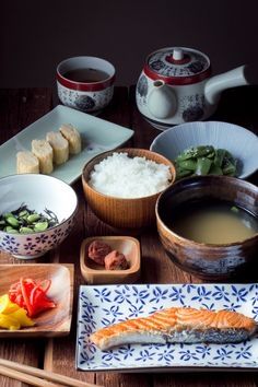 A traditional Japanese breakfast, which includes fish, rice, miso soup, and assorted vegetables.