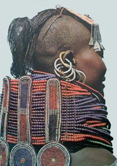 This type of multistrand necklace is worn by unmarried girls of marriageable age. Turkana woman wearing beaded necklace, Scanned postcard.