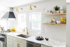 White and gold kitchen features white shaker cabinets adorned with brass pulls paired with calcutta marble countertops and a white subway tile backsplash. Kitchen Cabinets Decor, Farmhouse Kitchen Cabinets, Modern Farmhouse Kitchens, City Farmhouse, Cabinet Decor, Farmhouse Style, Rustic Farmhouse, Kitchen Windows, Grey Kitchens