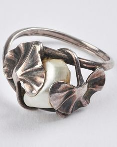 Dumont - An Art Nouveau silver and mother of pearl ring, circa 1900. Designed as two gingko leaves holding a mother of pearl at the centre. Signed DUMONT.
