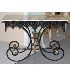 French antique wrought iron bakers' table with black painted base and grey marble top. The base has beautiful ornamental curving filigree with brass accents. The curvaceous design is carried out throughout the base. Origin : France Circa : 1890s 42.5 w 22.5d 30.25 h $2500