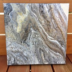 Original, abstract, acrylic fluid painting on canvas. Liquitex pouring medium, floetrol, acrylic paint and a touch of silicone was used to create this one-of-a-kind piece. The colors used are black, white, pearl, gold, and champagne. Canvas size: 10 x 10 x 1.5 inches Sealed, painted