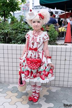 Her outfit features an Angelic Pretty strawberry print dress with ribbon print tights and red lolita bow shoes. Accessories include her super-kawaii strawberry cake hat/headpiece, strawberry hair clips, a Baby The Stars Shine Bright hair bow, a strawberry necklace, lace cuffs, a bow ring, Angelic Pretty strawberry rings, a cute straw purse (with another BTSSB bow), and a red Angelic Pretty polka dot bow purse.