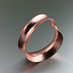 #Anticlastic Hammered #Copper #Bangle Bracelet - Wrap your wrist in modern elegance when you don this beautiful Hammered Copper Bangle. This bold copper cuff bracelet showcases a tapered anticlastic silhouette with a chic backdrop of hand-hammered detailing. The tantalizing texture and clean lines lends a contemporary feel to the stylish piece. $180 http://www.ilovecopperjewelry.com/anticlastic-hammered-copper-bangle-bracelet.html