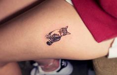 Small cat tattoo on the left thigh.
