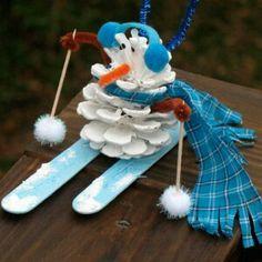 Materiaal: dennenappel. Twee ijsstokjes. Twee hakve sateprikkers.pijpenragers. lapjes en witte verf.